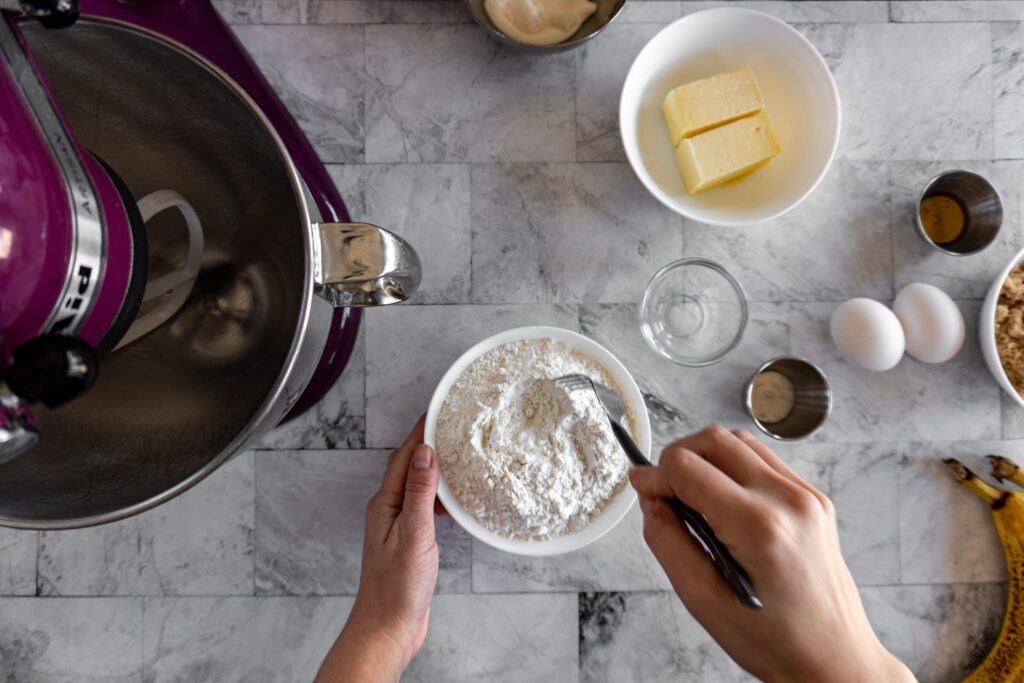 Whisking dry ingredients together in a small white bowl.