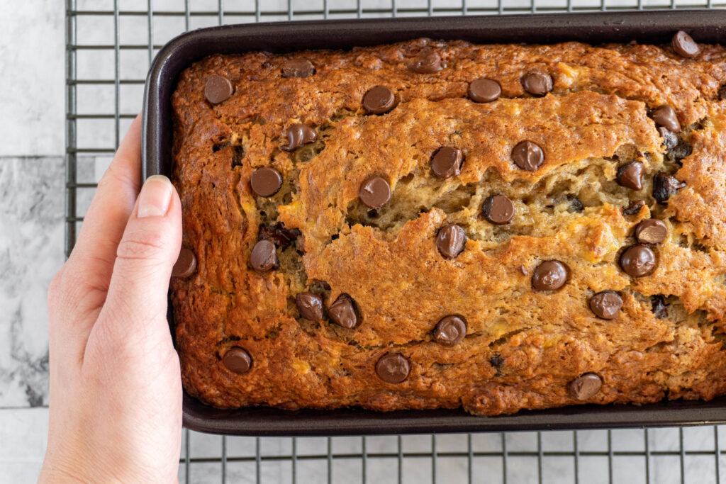Hands holding a baking pan with baked banana bread.