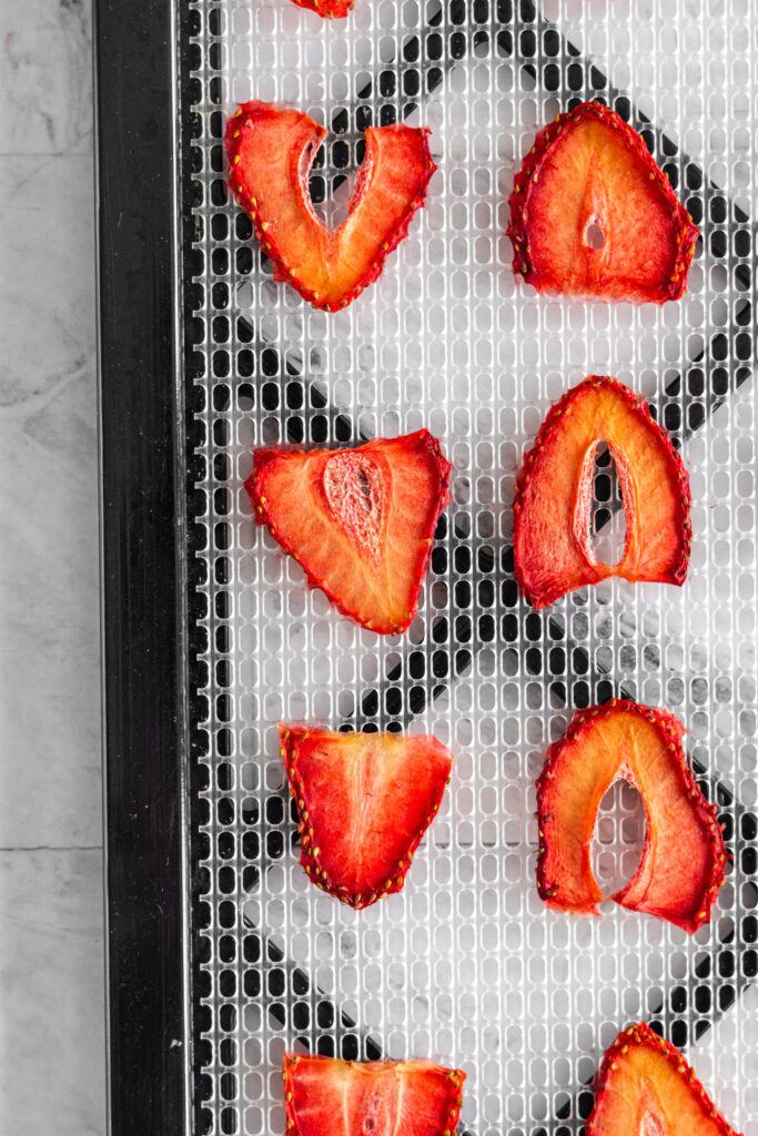 Dehydrated strawberries on a mesh dehydrator tray.