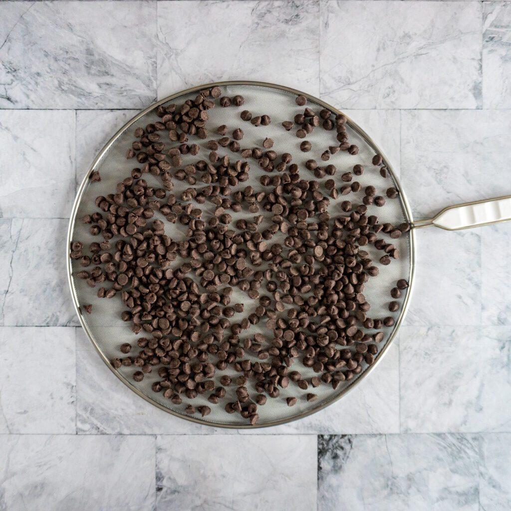 Spreading chocolate chips on a splatter screen.