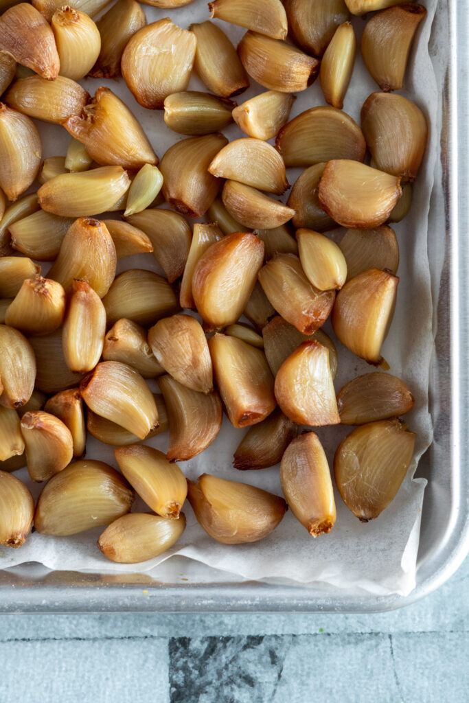 Smoked garlic cloves piled in a small baking sheet lined with parchment paper.
