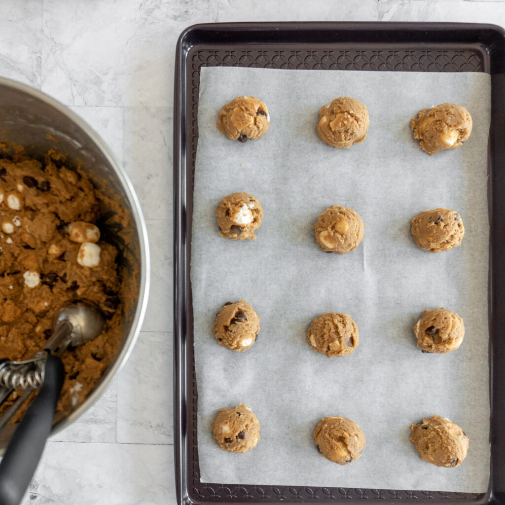 Cookie dough balls scooped onto a baking sheet.