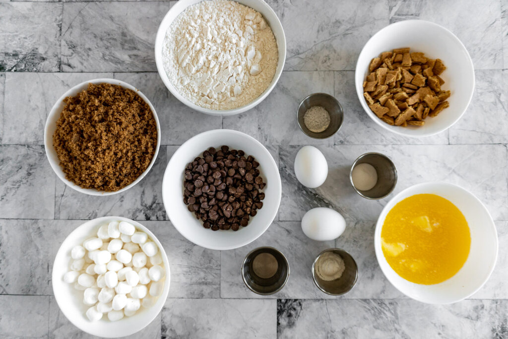 All the ingredients required for s'mores cookies pre-portioned and displayed on a counter top.