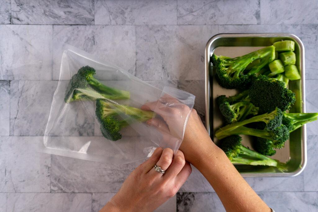 Adding broccoli to the vacuum bag.