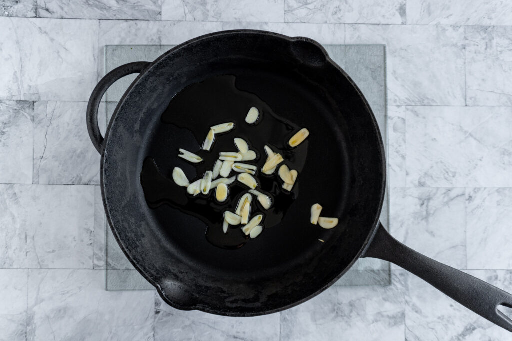 Sliced garlic and olive oil in a large cast iron skillet.