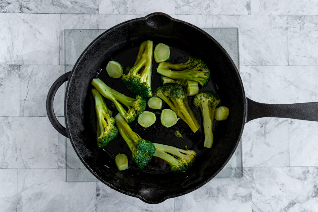 All the broccoli in the skillet after being slightly sauteed.