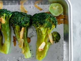 Sous vide broccoli in a mini sheet pan topped with browned garlic