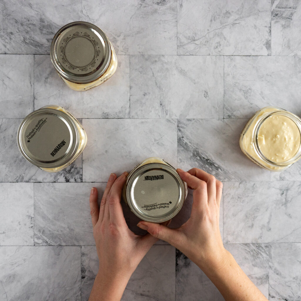 Screwing lids on to the prepared jars.