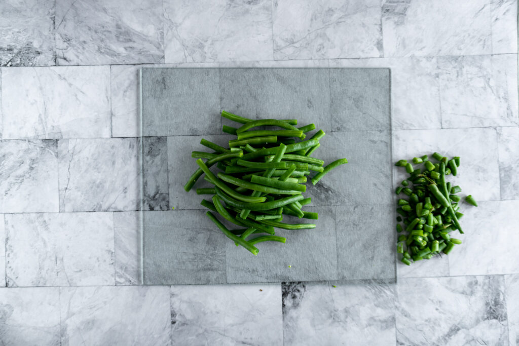 Fully chopped green beans on a glass cutting board.