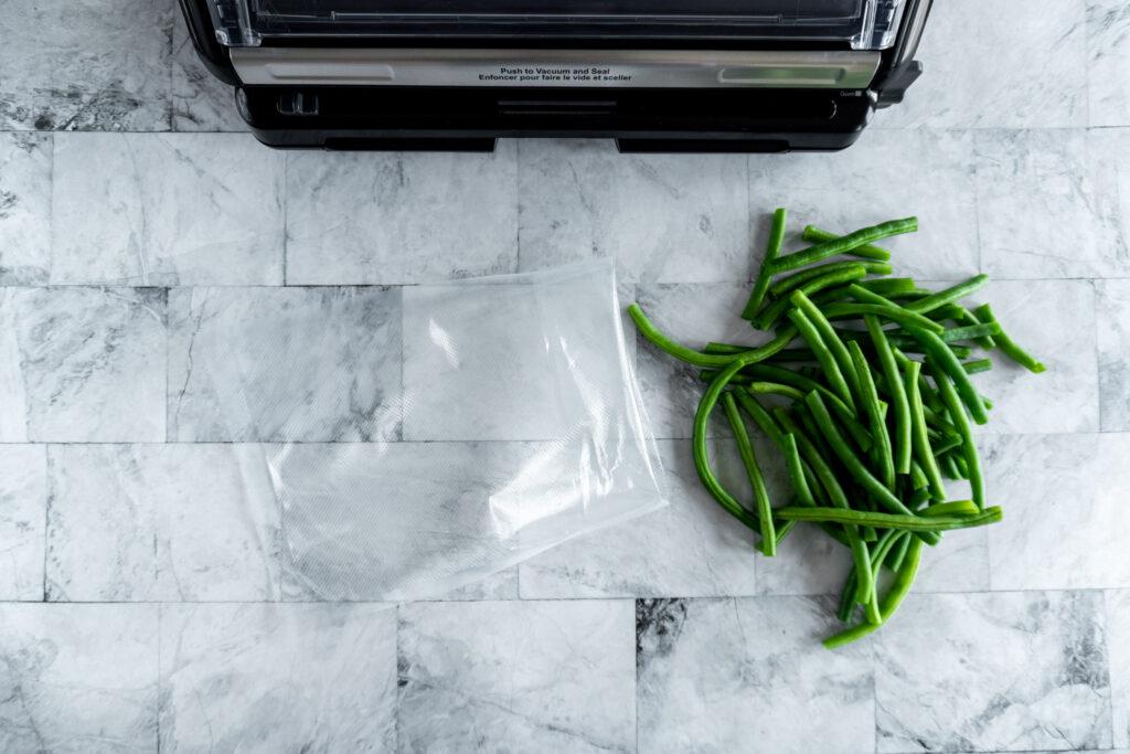 A vacuum seal bag beside prepared green beans.