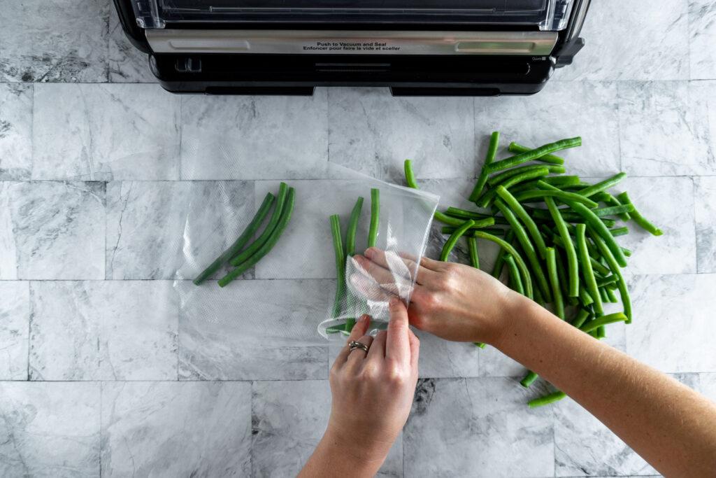 Adding prepared green beans to vacuum seal bag.