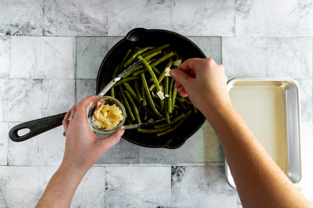 Sprinkling the chopped parmigiano regianno on the green beans.