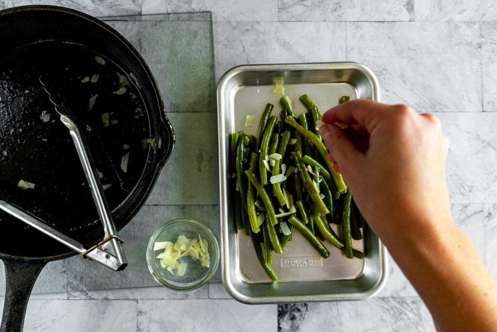 Adding remaining cheese petals to the plated green beans.