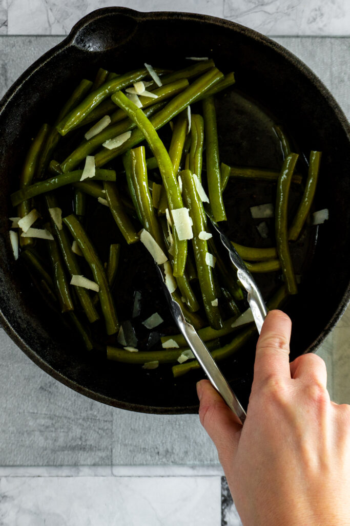 Picking up the green beans with tongs to move to serving tray.