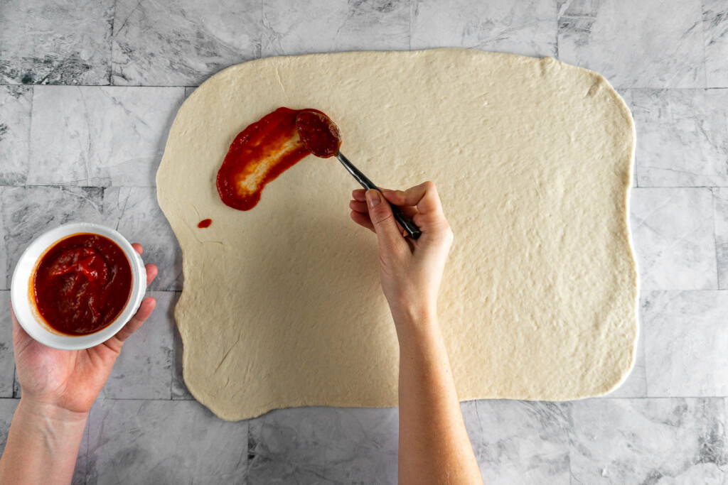 Spreading pizza sauce on the dough.