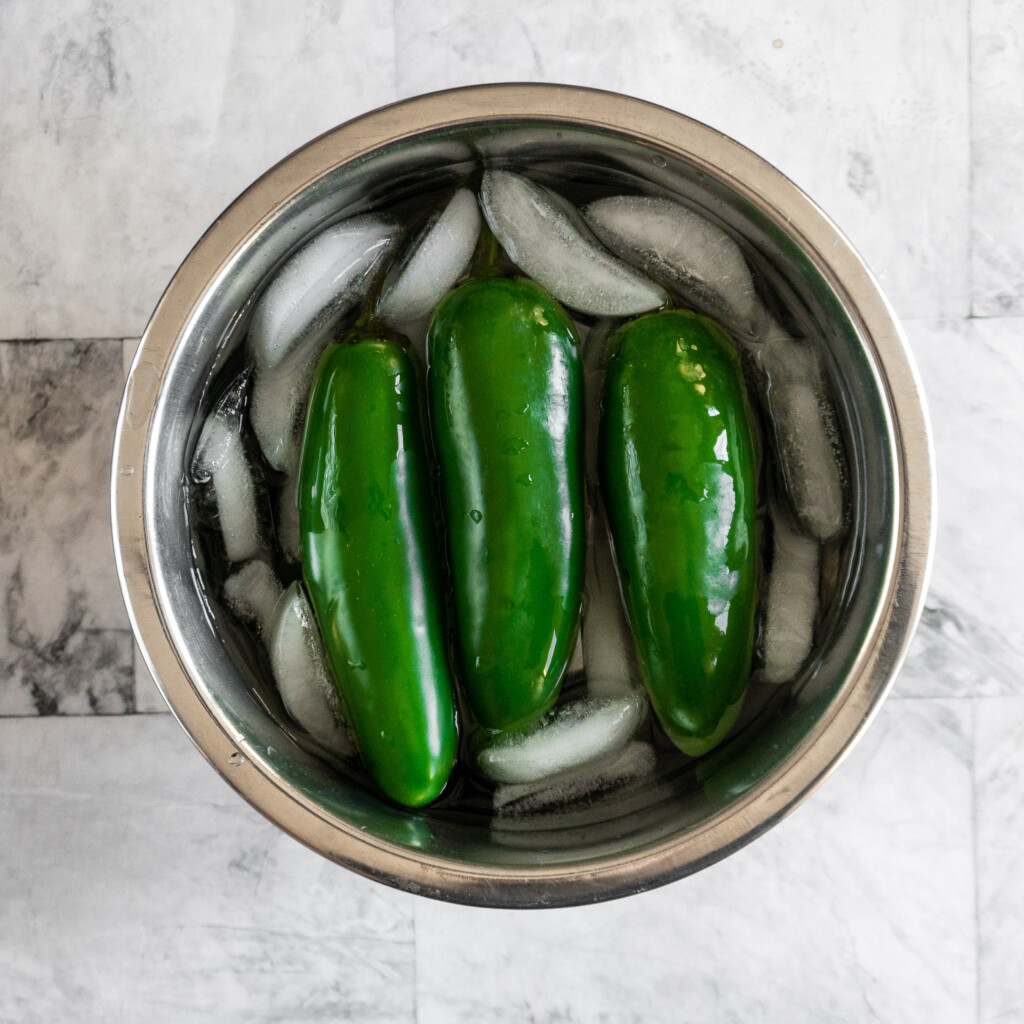 3 jalapenos in a small bowl with ice water.