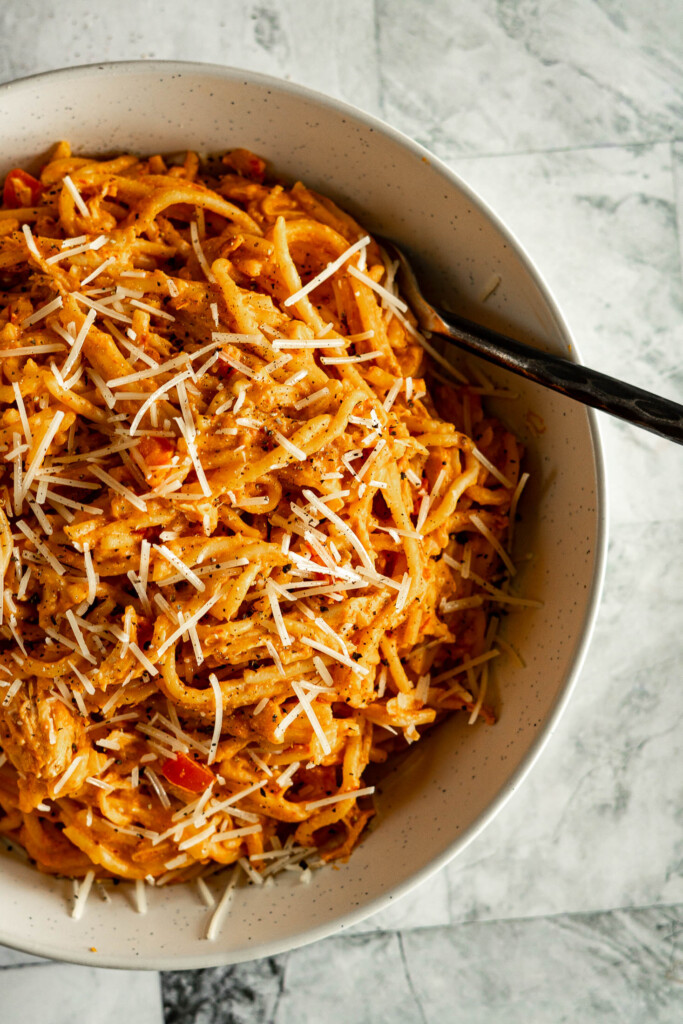 Instant pot chicken spaghetti in a bowl garnished with shredded asiago.