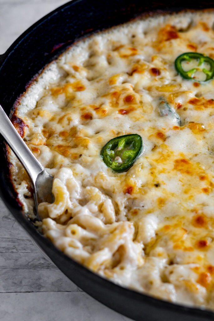 A spoon stirring cooked jalapeno monterey jack mac and cheese.