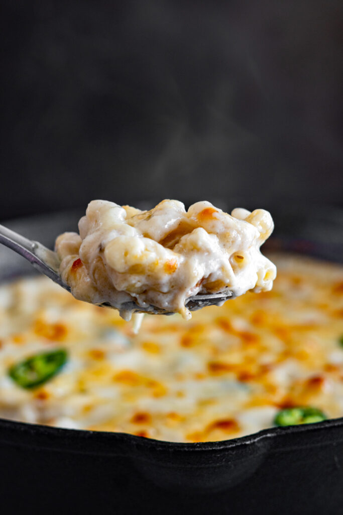 A spoon full of pepper jack mac and cheese steaming.