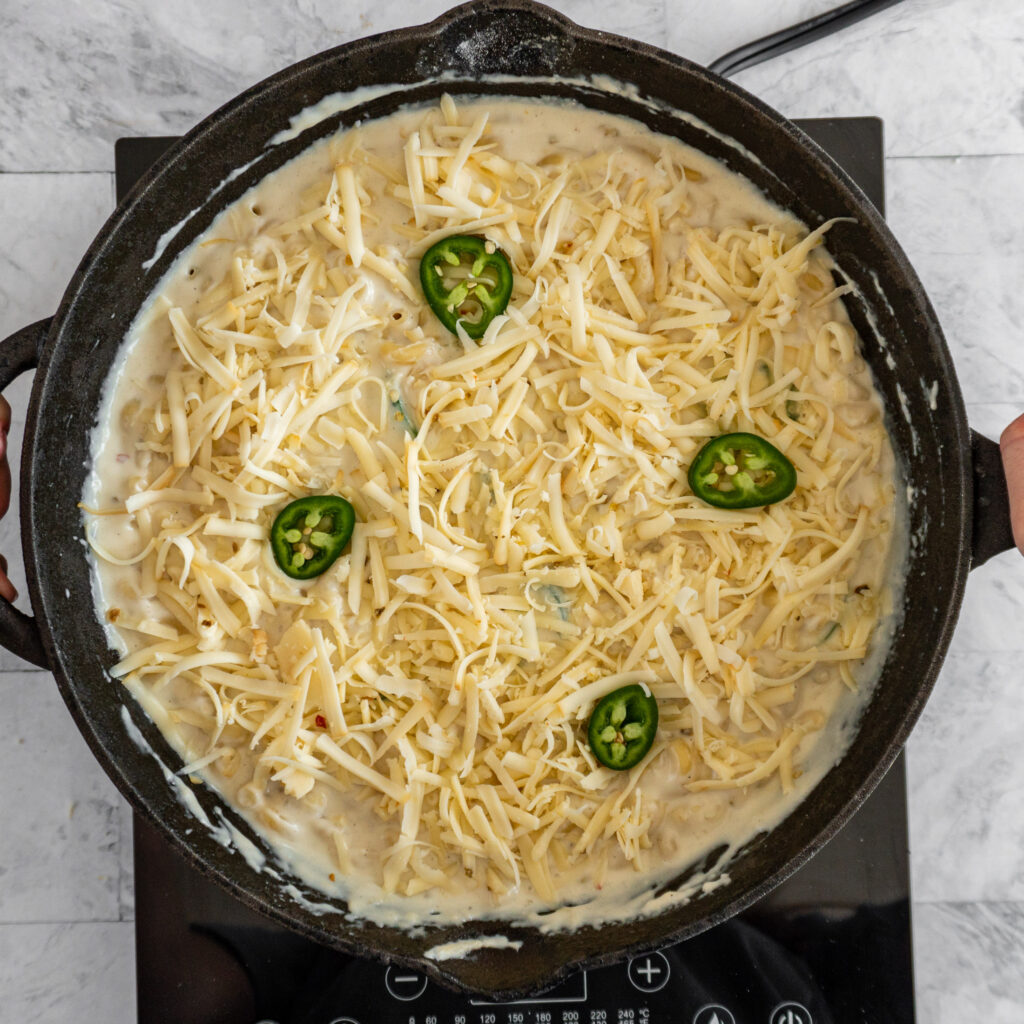 Mac and cheese topped with reserved cheese and a couple slices of jalapeno ready to go into the oven.