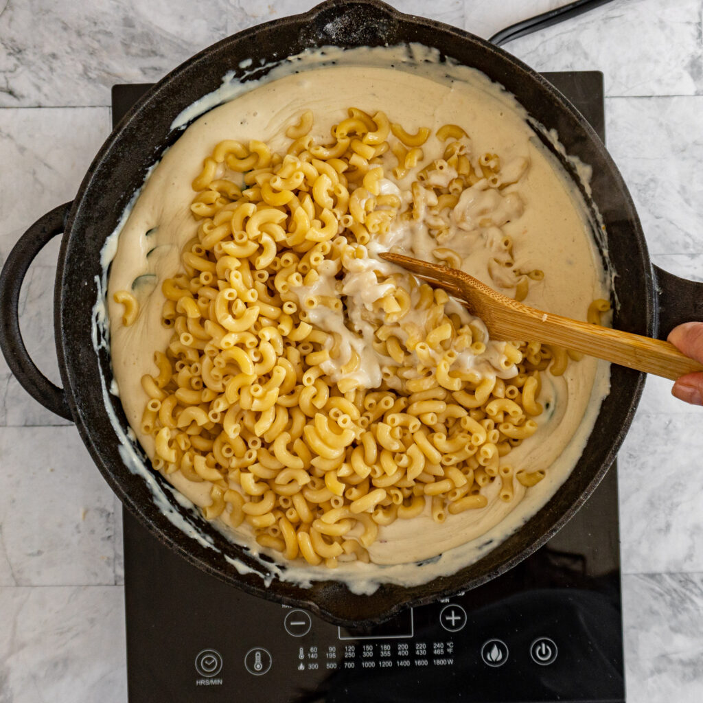 Stirring macaroni noodles into the cheese sauce.
