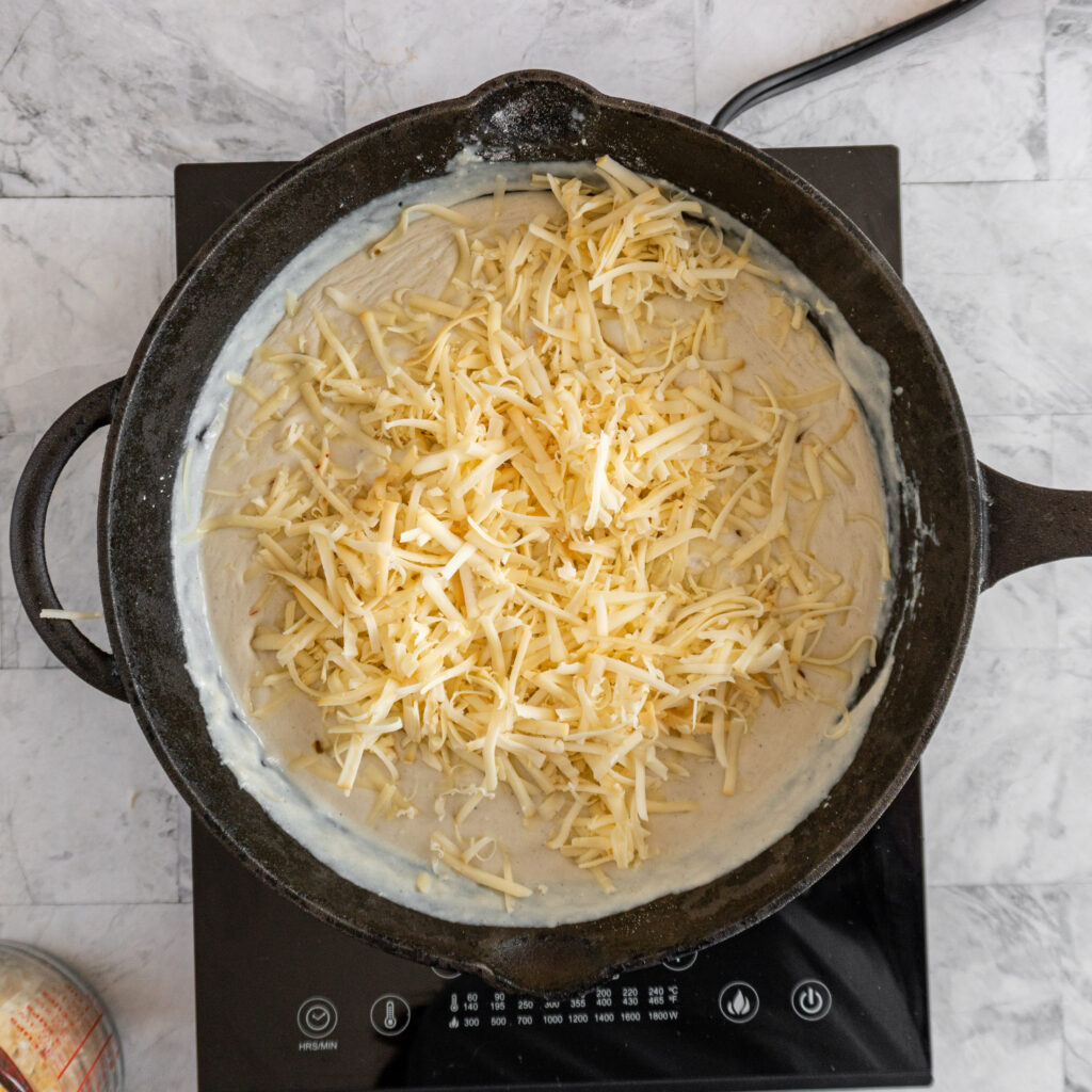 Adding cheese to the skillet.