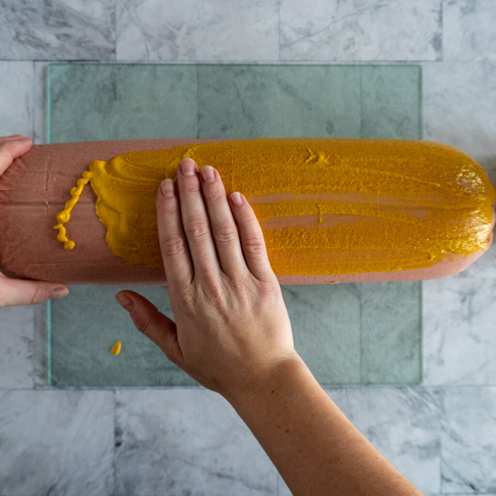 Hands rubbing the bologna with mustard.