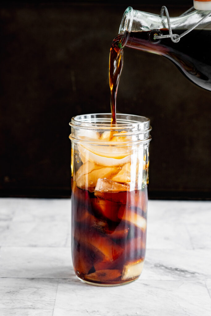 Pouring cold brew coffee into a large mason jar filled with ice.