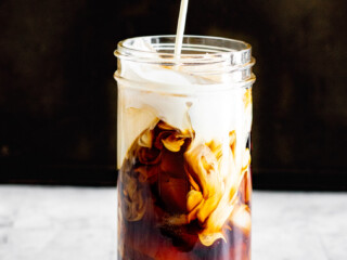 Pouring cream into a jar filled with cold brew sous vide coffee and ice