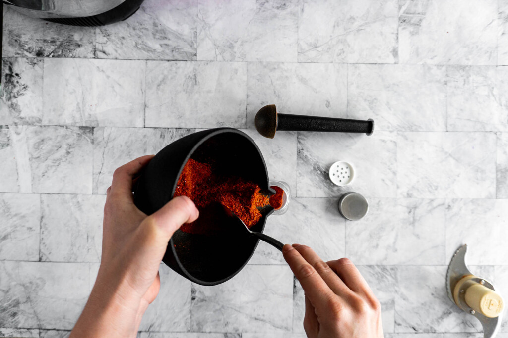 Transferring sriracha powder from mortar and pestle to a shaker jar.