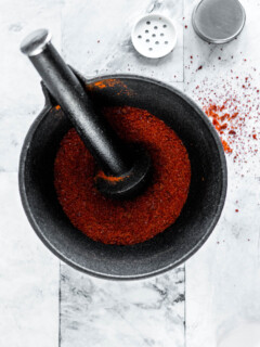 Sriracha powder in a mortar and pestle.