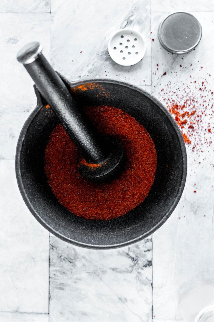 Sriracha powder in a mortar and pestle.