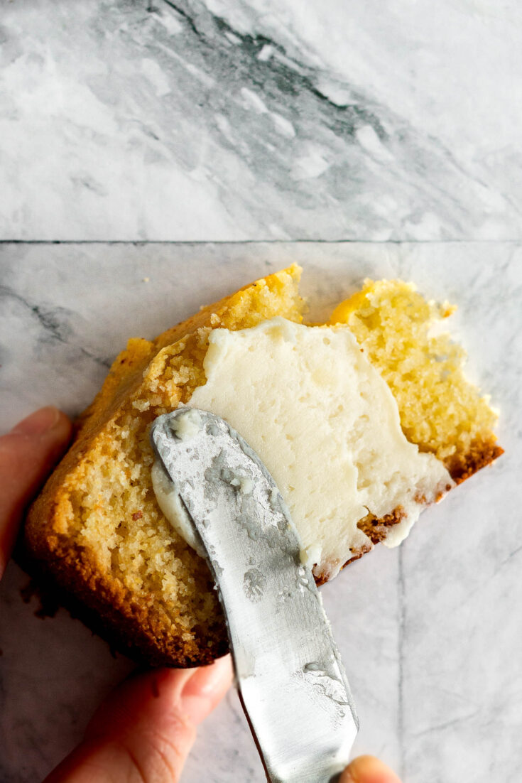 Spreading whipped honey butter on a slice of cornbread.
