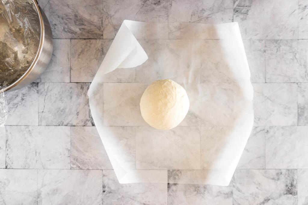 Sourdough boule placed seam side down on a piece of parchment paper.