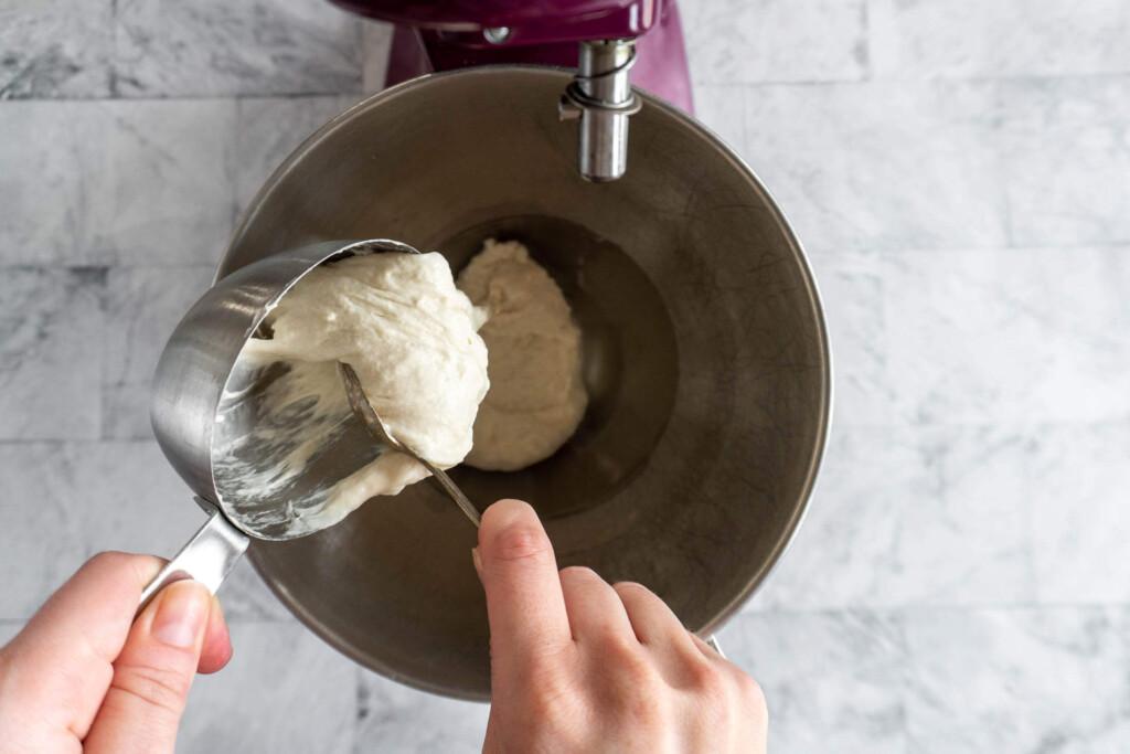 Adding sourdough starter to a mixing bowl.