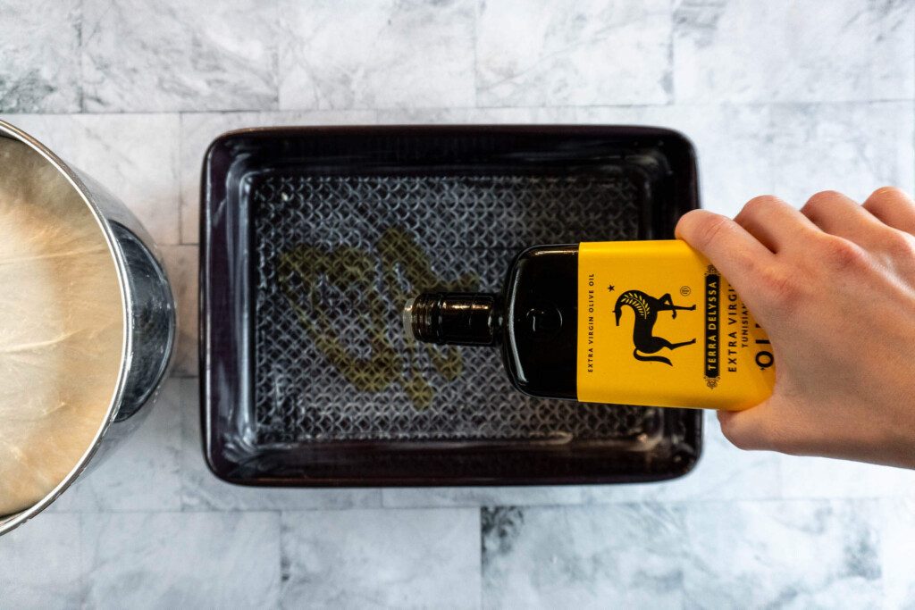 Drizzling baking dish with olive oil.