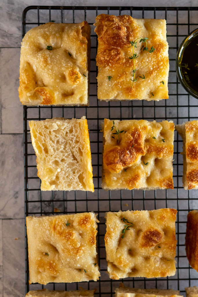 Sliced sourdough focaccia on a wire mesh rack with balsamic oil for dipping.