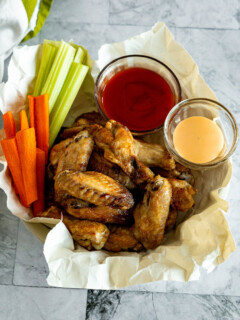Frozen air fryer chicken wings in a bowl with hot sauce and celery sticks.