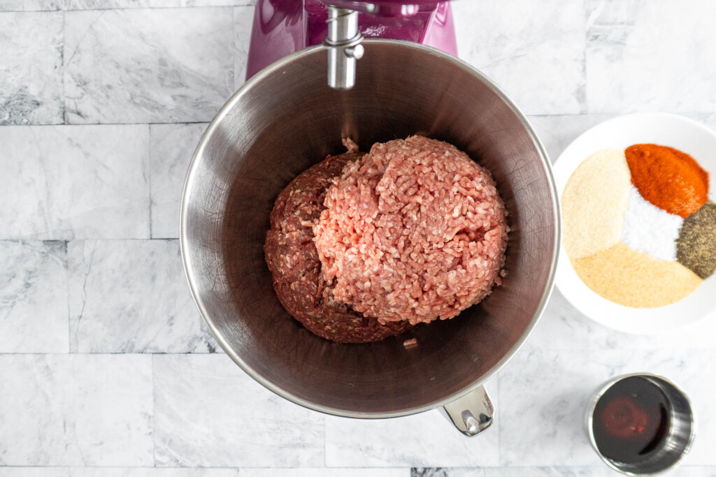 Ground beef and ground pork in the bowl of a stand mixer.