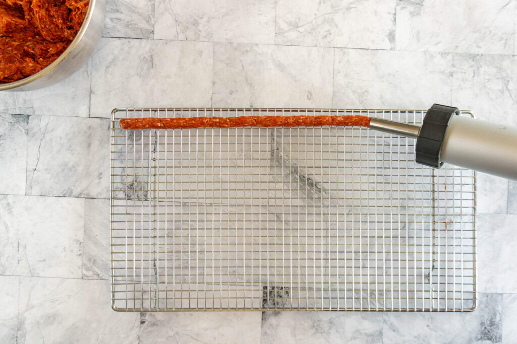 Piping out tubes of ground beef jerky onto a wire mesh rack.