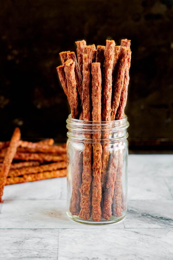 Ground beef jerky sticks in a mason jar.