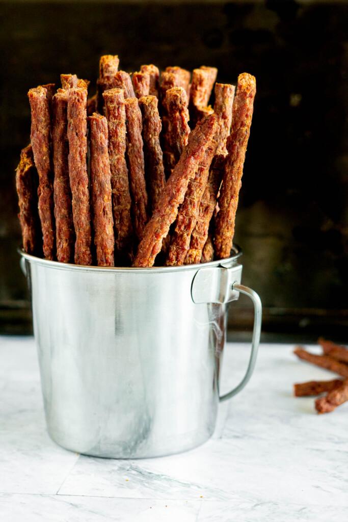 Beef jerky sticks in a tin bucket.