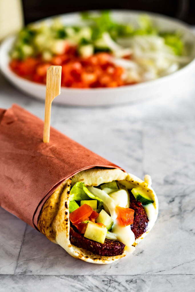 A wrapped donair in front of a plate of chopped veggies.