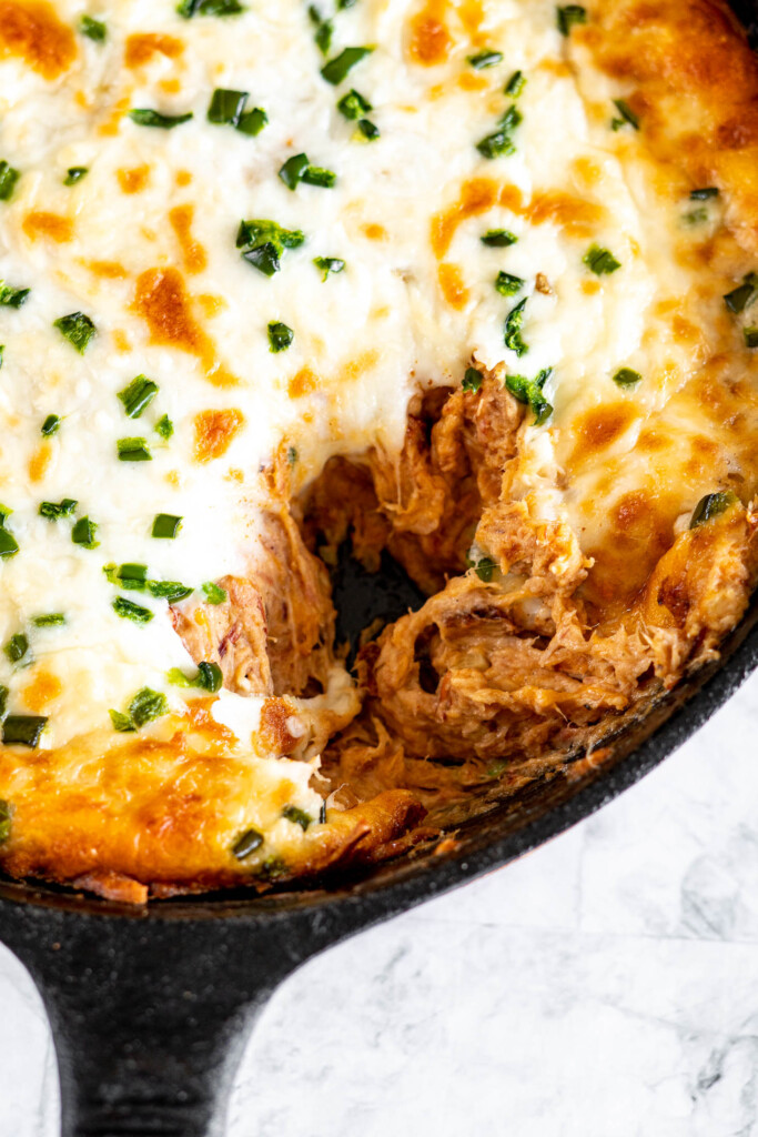 A cast iron pan filled with pulled pork dip missing a scoop.