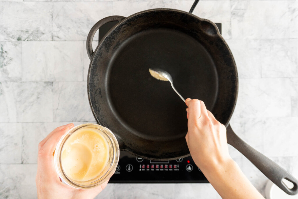 Adding bacon fat to a hot cast iron skillet.