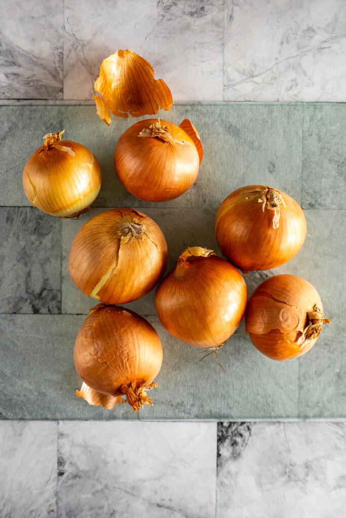 Fresh yellow onions on a cutting board.