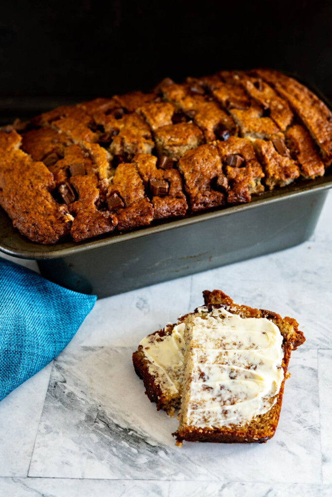 Sliced sourdough banana bread slathered with butter.