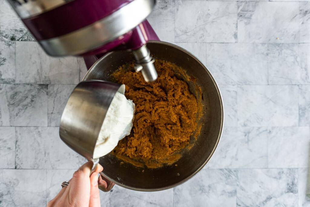 Adding sourdough discard to the mixing bowl.