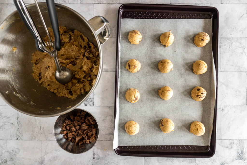 Scopping the cookie dough into balls onto a prepared cookie sheet.