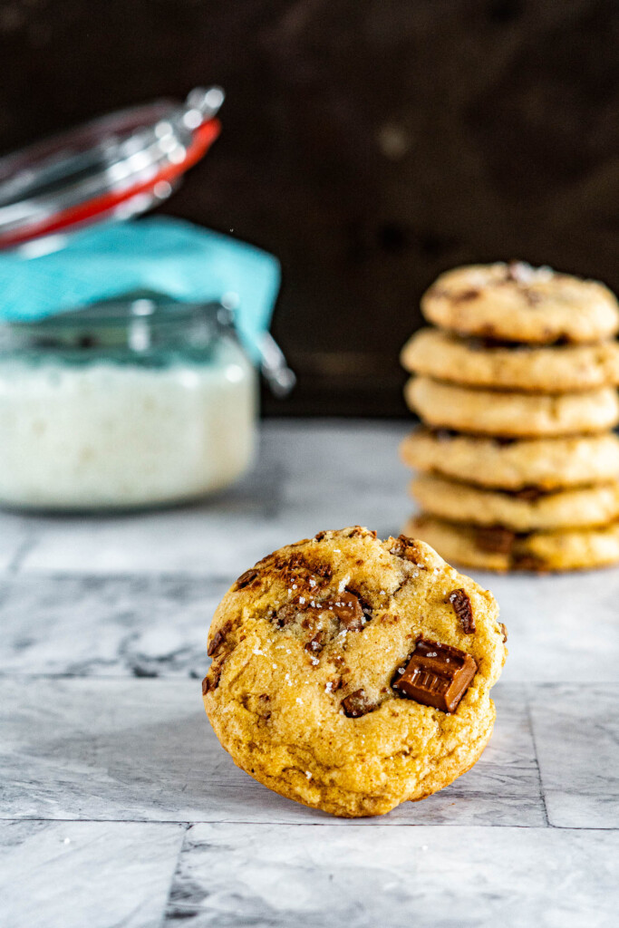 A stack of chocolate chip cookies in front of sourdough starter.